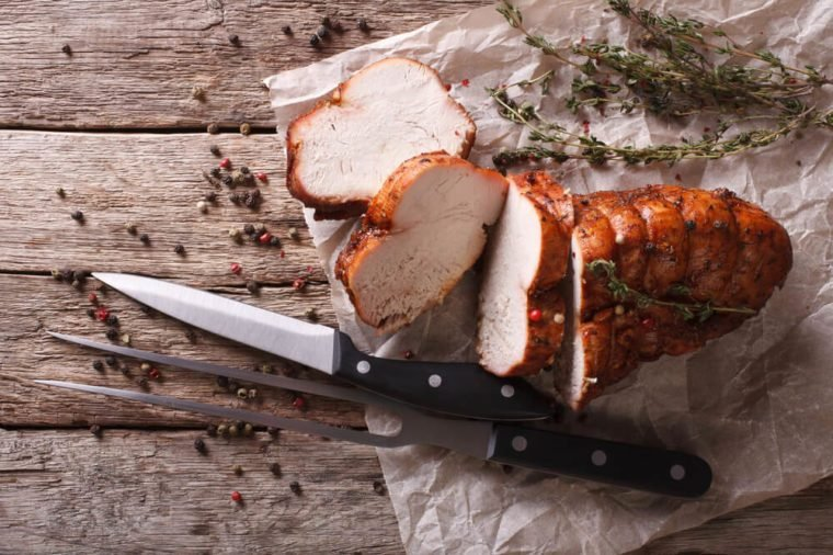 rustic food: roasted turkey breast on a paper on the table. horizontal top view
