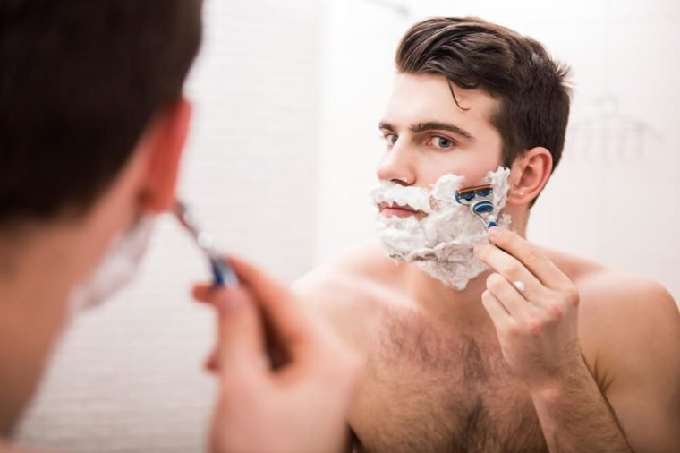 Handsome young man is shaving his face and looking at the mirror.