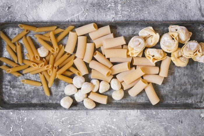 raw italian pasta variety overhead uncooked gluten free pasta on baking dish