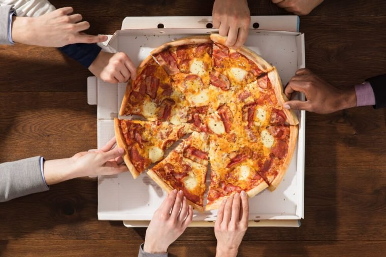 Group Of Hands Taking Each Slice Of Pizza From The Box