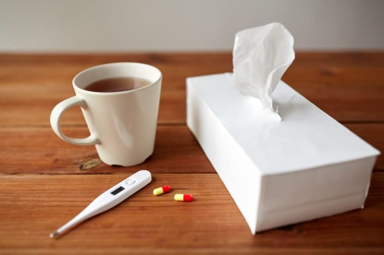 healthcare, medicine, flu and treatment concept - cup of tea, paper wipes and thermometer with pills