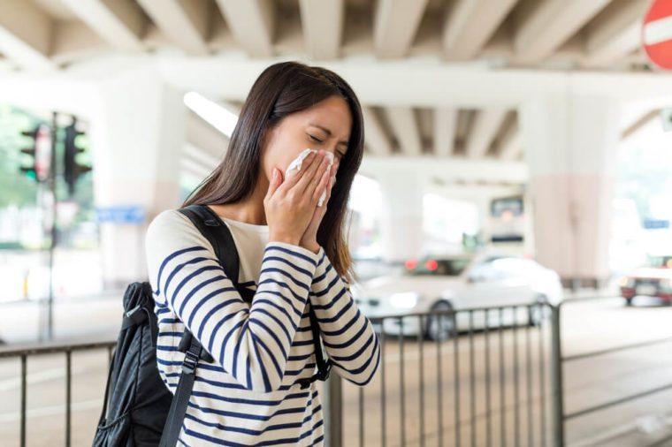 Woman sneezing in Hong Kong city