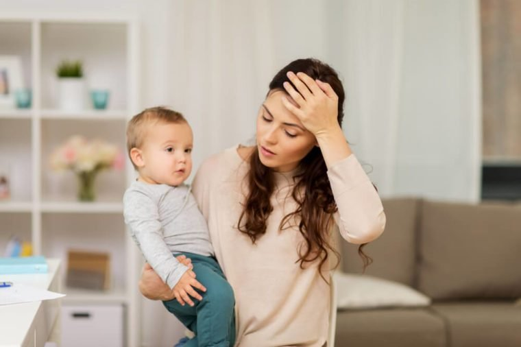 motherhood, multi-tasking and family concept - tired mother having headache with baby boy at home