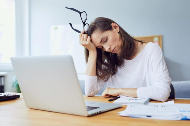 tired young office worker falling asleep at her desk while trying to work in modern office