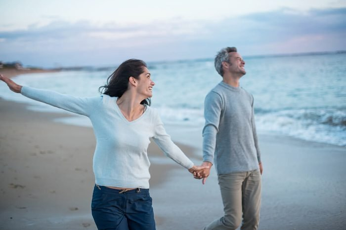 Beautiful couple walking on the beach at sunset. They are barefoot and wearing casual clothes