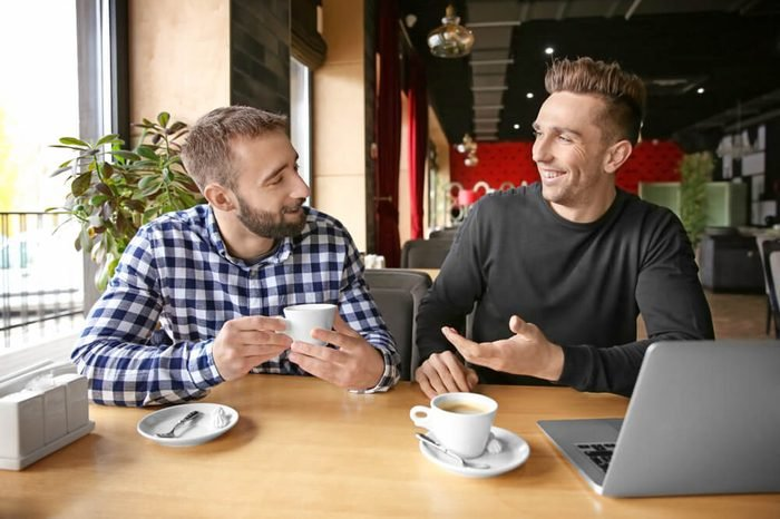 Young hipster men with coffee and laptop in cafe