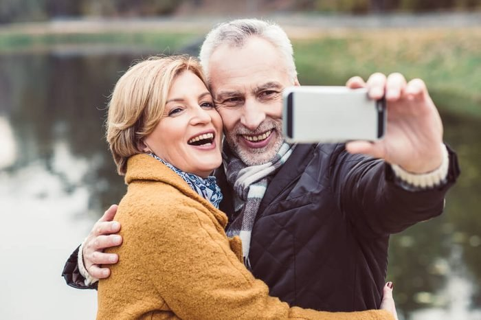 Close-up portrait of happy mature couple taking selfie in autumn park