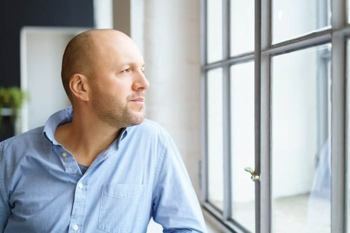 Middle-aged man watching through a window with a thoughtful expression as he leans on the sill