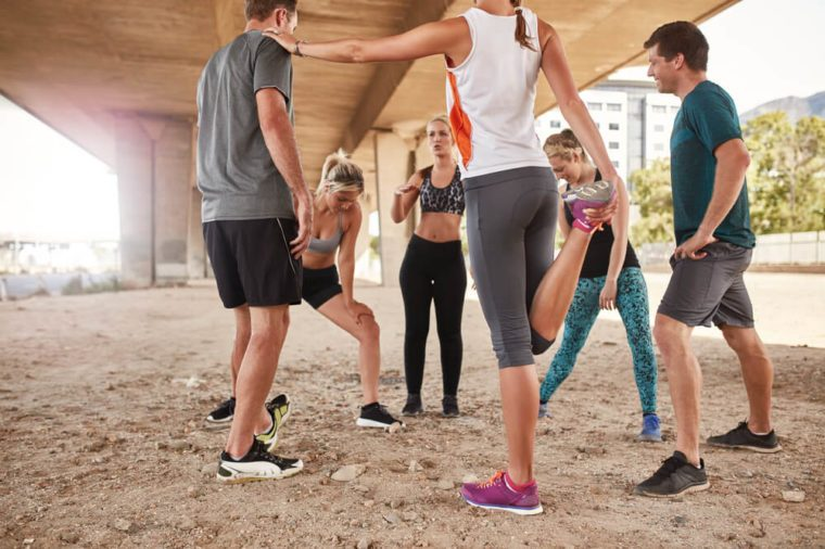 Group of young friends stretching under a bridge after a morning run. Running club group taking a break from training.