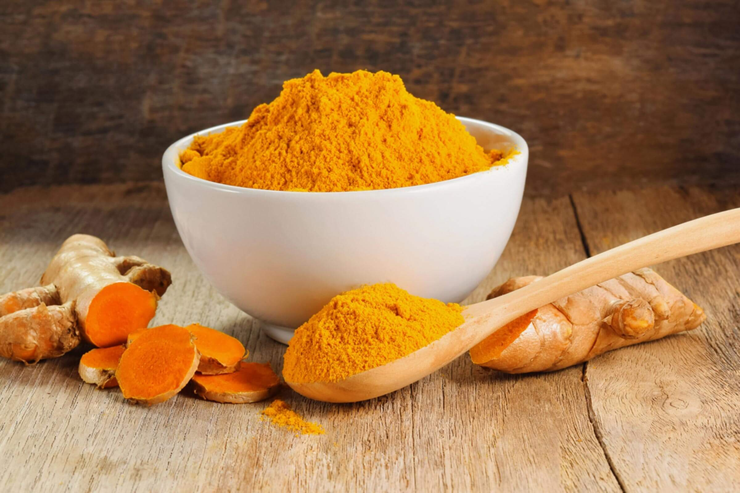 Turmeric powder in a bowl surrounded by the root and a wooden spoon