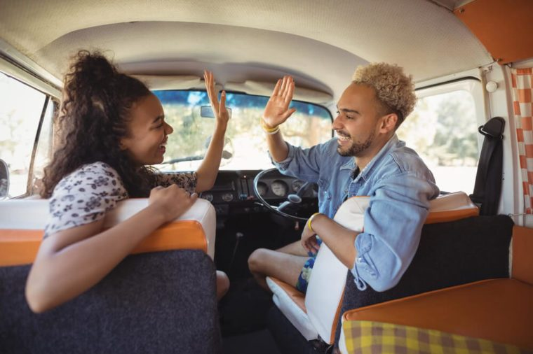 Happy friends giving high-five while sitting in mini van