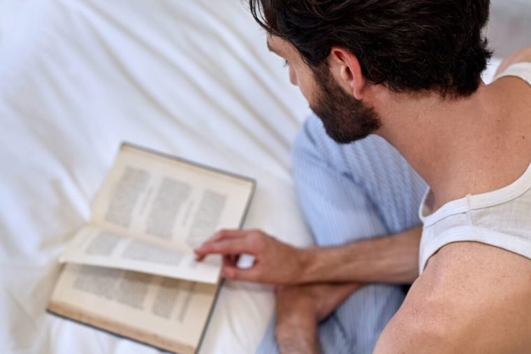 man relaxing on bed reading literature novel story book at home