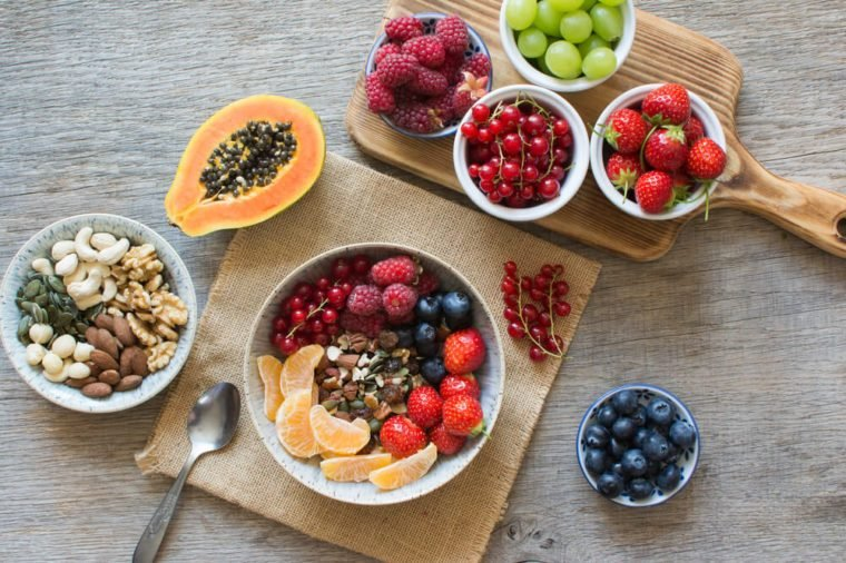 Overhead view of paleo style breakfast, grain free granola made with nuts and dried fruits, served with fresh berries, selective focus