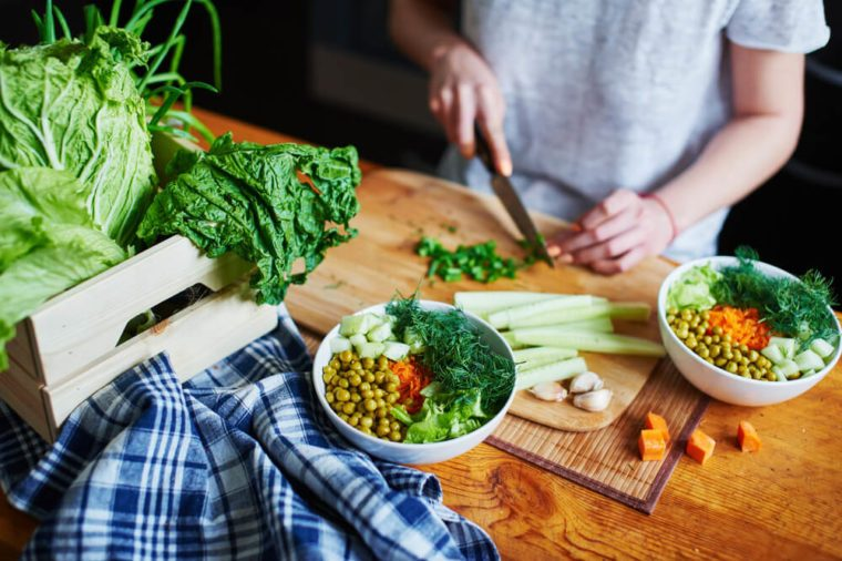 Bowl with green peas, cucumbers, carrots, lettuce and dill standing on a table on a background of hand chopping green onions with knife on wooden Board