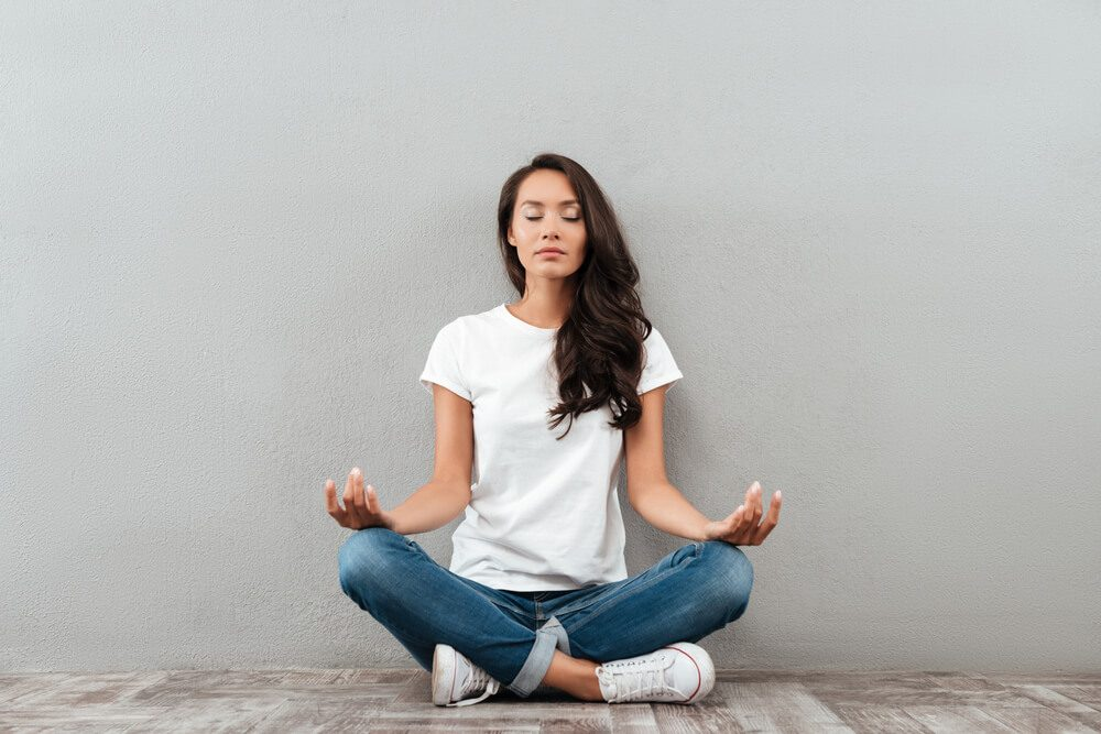 Beautiful young asian woman sitting in yoga position and meditating isolated over gray background