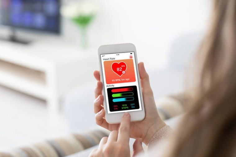 Female hands holding phone with app health tracking activity on screen in room