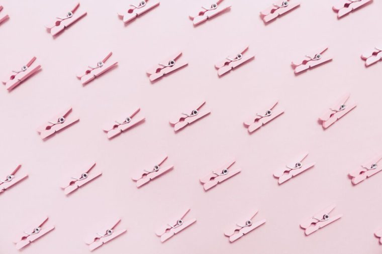 Pink clothes pins on the pink background. Horizontal