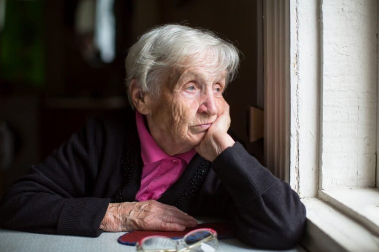 An elderly woman sadly looking out the window. Melancholy and depressed.