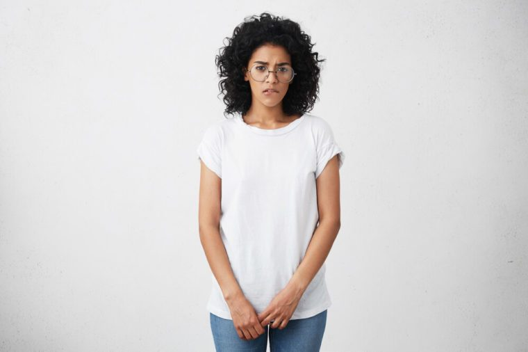 Shy and timid African American student girl wearing glasses, white t-shirt and jeans having indecisive confused look while answering to teacher's question in class, biting lips, feeling nervous