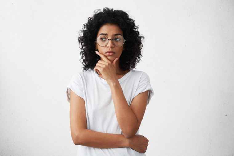 Portrait of beautiful casually dressed young woman in round glasses having doubtful expression, looking away in indecisiveness, holding her chin, trying to find best solution. Body language