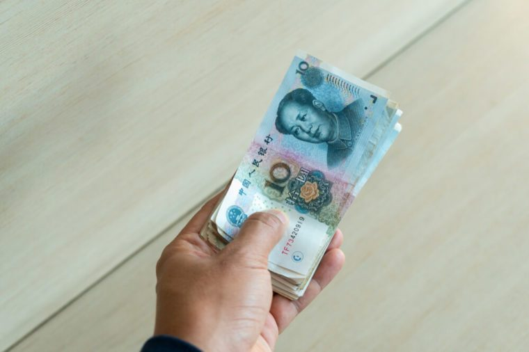 Hand holding Chinese Yuan Note (rmb or renminbi) with pay