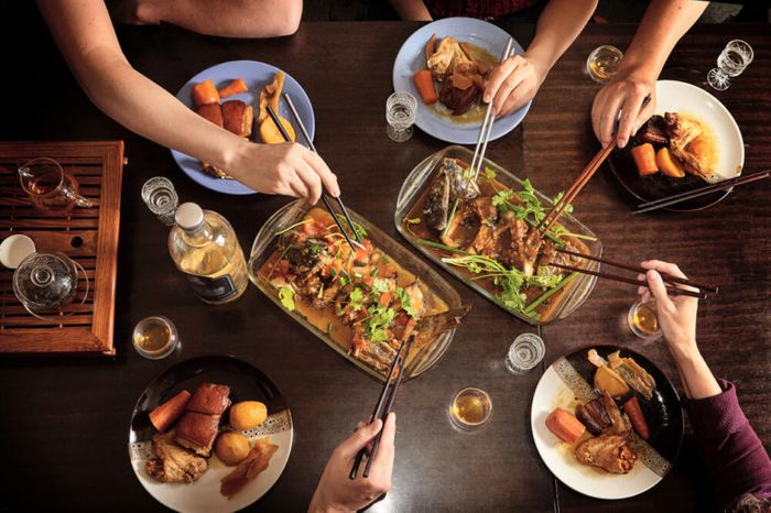 Dinner with friends at the table. View from above. Chinese food with chopsticks. fish, meat, pork, potatoes.