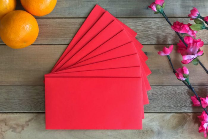 Chinese New Year concept. Red envelope (ang pao), mandarin oranges and flower on a wooden table.
