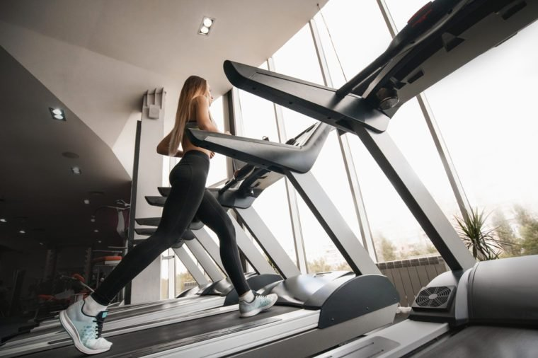 Young slim woman running on treadmill. Beautiful young woman in gym. Running in sport club. shapely pair of legs.