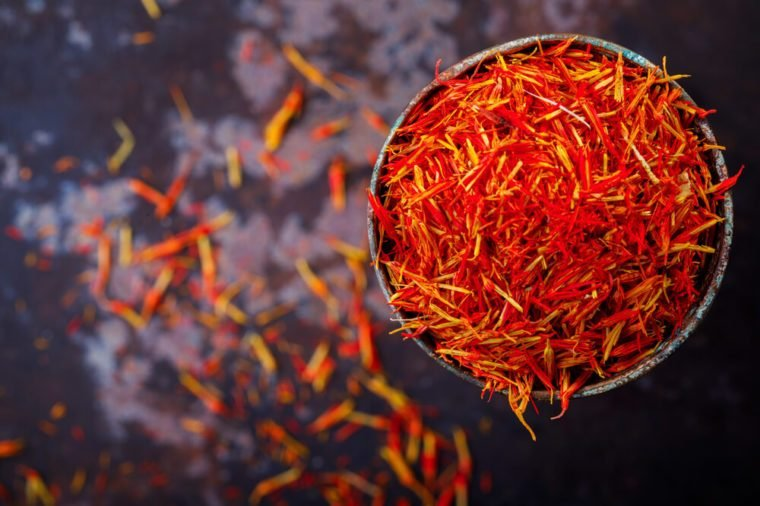 Dried saffron spice a glass of metal Oriental flavor. Raw Organic pistil powder saffron Red Exotic Seasoning on black background Dull pestle of orchid flower.