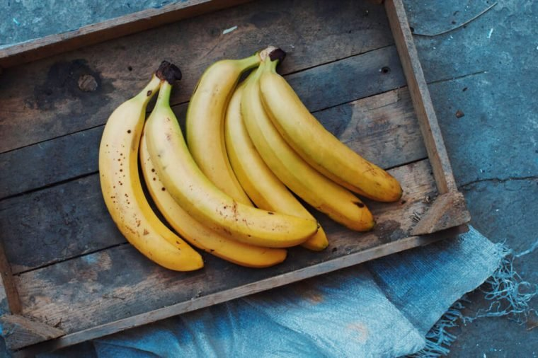ripe yellow bananas in wicker basket, on wooden background, view from above, yellow fruits, yellow bananas in a wooden box, food, meal, vitamins,