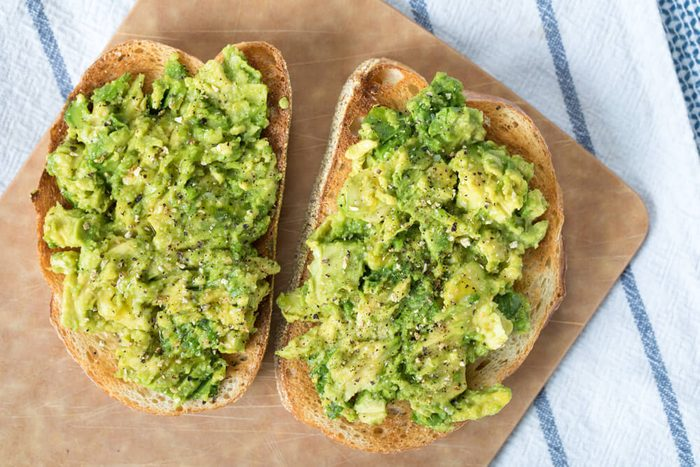 Over head avocado toast on slices of toasted French loaf bread topped with ground lemon pepper and sprinkles of kosher salt on wood cutting board on top blue and white striped linen cloth