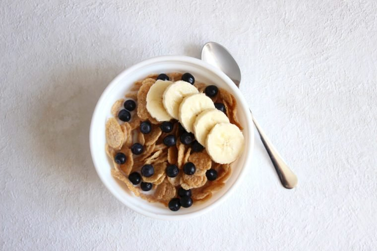 A Bowl of Cereal on white background. Breakfast Bowl of Cereal with Banana, Blueberries and Milk. Eating cereal. Healthy breakfast food.