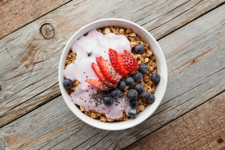 bowl of muesli with yogurt and berries on wooden table, top view