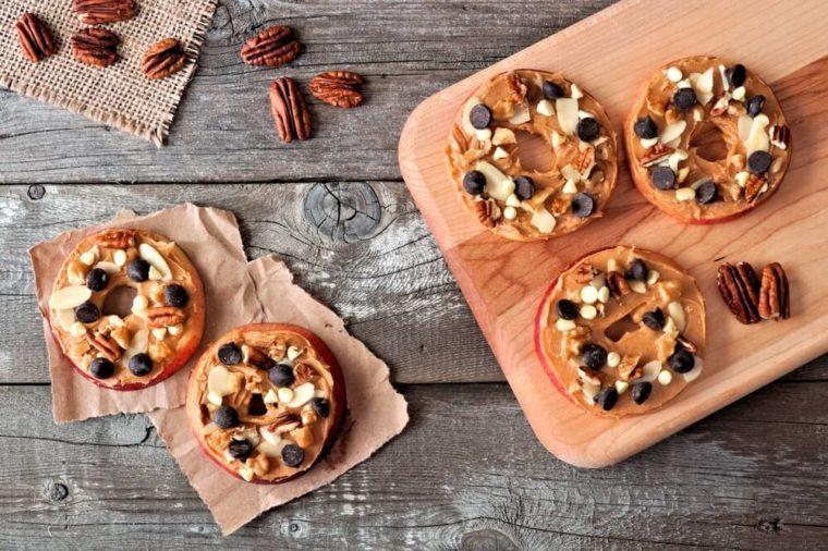Autumn apple rounds with peanut butter, chocolate chips and nuts, downward view on rustic wood