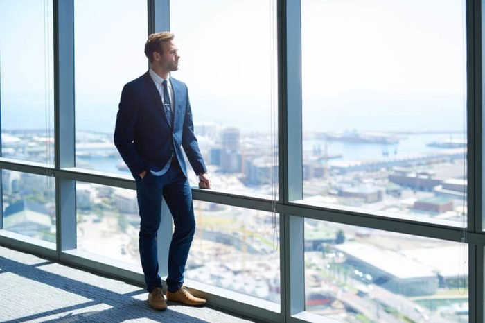 Full length shot of a stylish young businessman wearing a modern suit, who is a high achiever, standing on the top floor of an office building looking out at the view through large windows