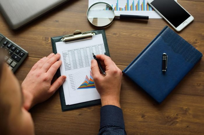 Financial printed paper charts, graphs and diagrams. Businessman (analyst) analyze graphs and charts.