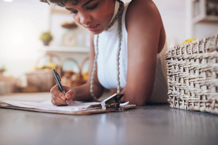 Cropped image of young african woman working in a juice bar. Female standing behind the counter and writing notes. Calculating a customer bill.