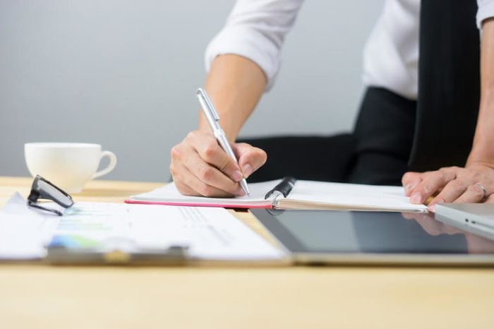 Business planning,male manager putting his ideas , writing marketing plan by holding pencil and papers on clip broad making notes in documents on the table in office,vintage color,selective focus.