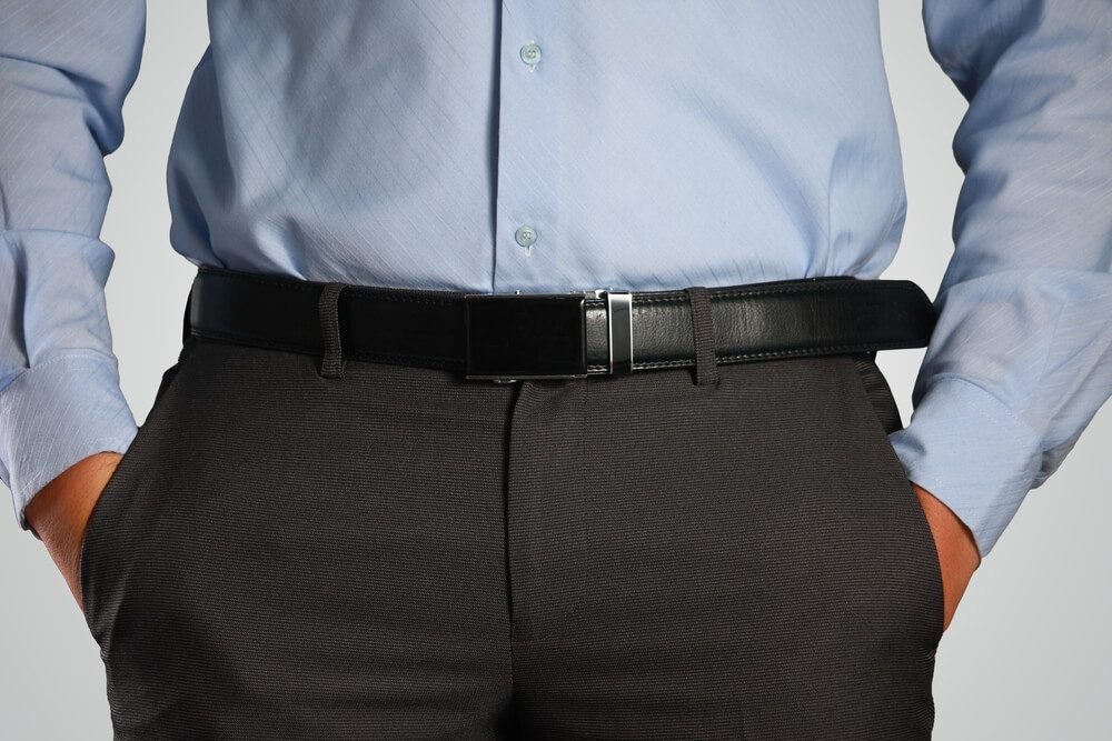 Photo image closeup shot of male waist with hands in pocket dressed in black pants, belt, blue shirt. Formal wear