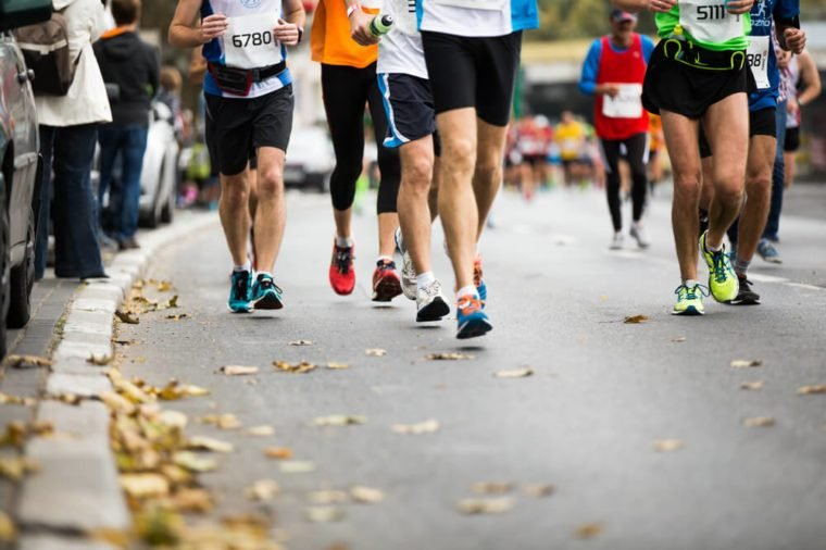 Marathon running race, people feet on autumn road