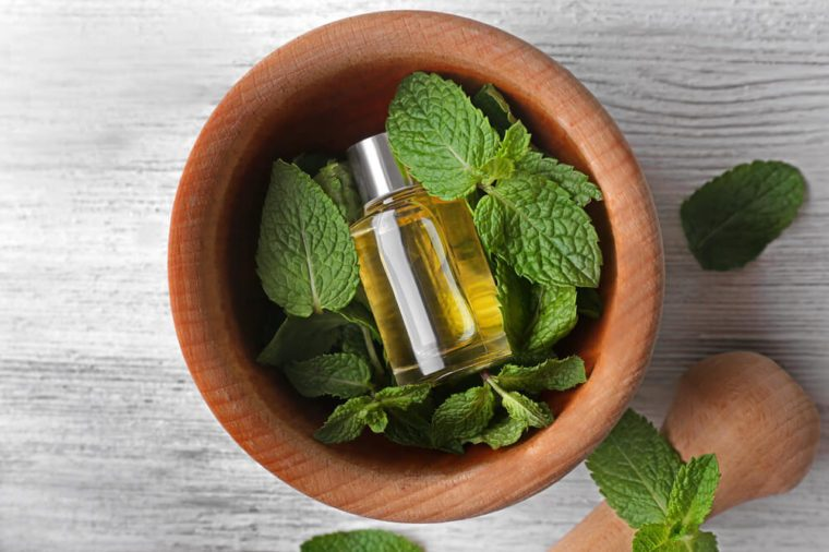 Essential oil with mint in mortar on wooden table