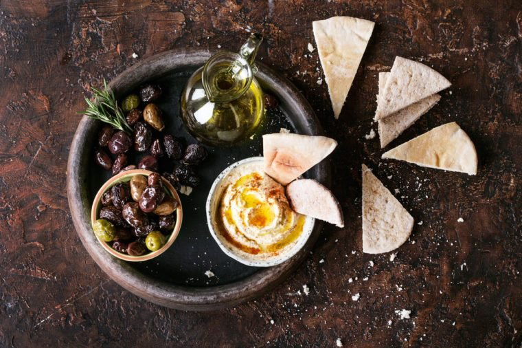 Traditional Middle east appetizer Hummus served with fresh pita bread, olives, herbs, seasoned with extra virgin olive oil and paprika in vintage cermic plate. Top View