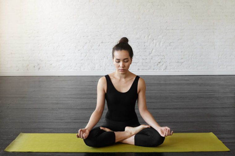 Beautiful asian young woman sitting in Lotos pose. Businesswoman practicing meditation in yoga hall after hard day, sitting in a prayer position on the green yoga mat. Time for Yoga and relaxation