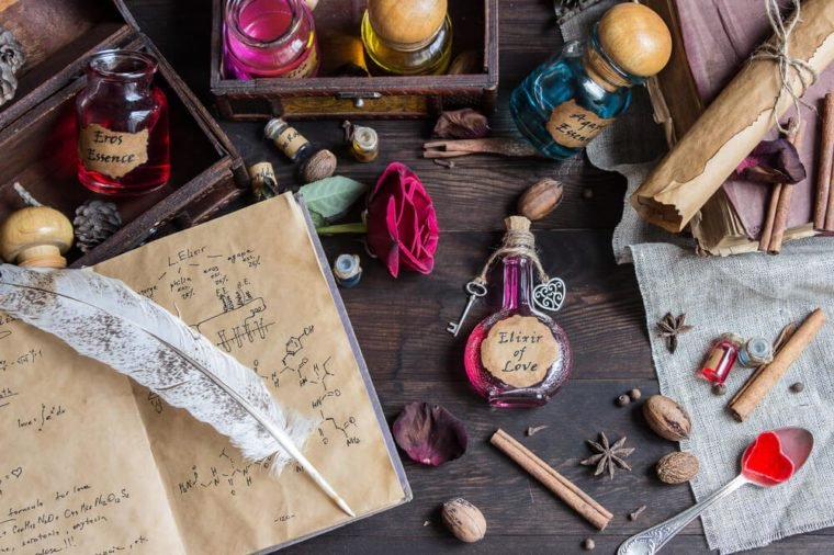 Preparing Elixir of Love on wood table. Spoon with red sweet heart, old books, flasks, bottles. Valentines Day and Love concept.