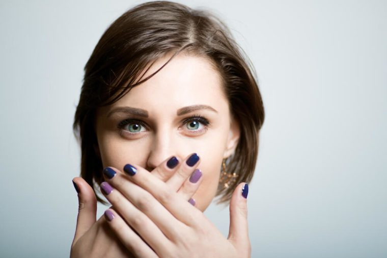 Pretty slender girl covers her mouth with her hands, lifestyle, isolated on a gray background