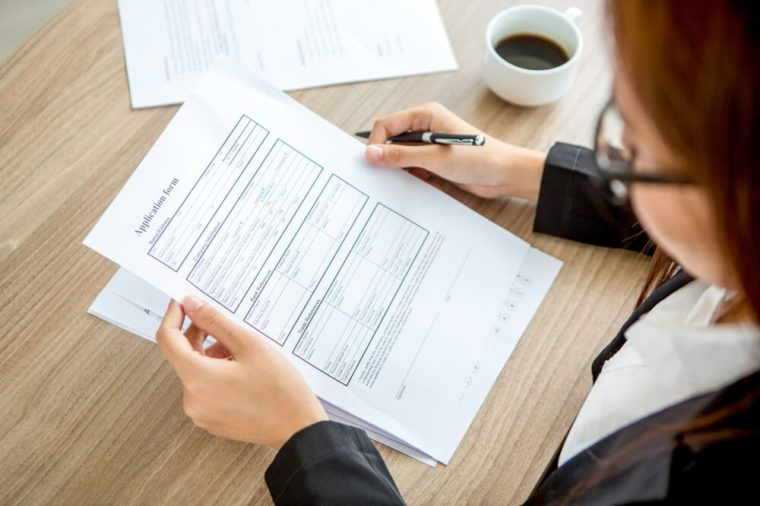 Young businesswoman reading application form