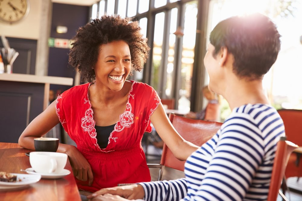 Two female friends talking at a coffee shop