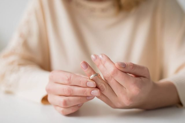 Woman divorcing and taking off wedding band