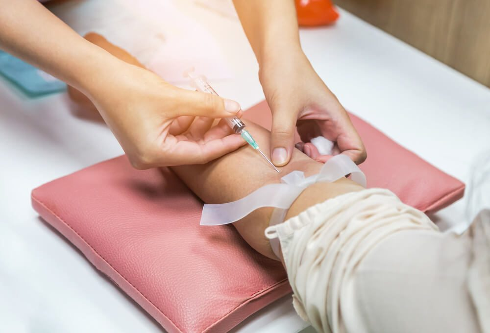 Close up nurse pricking needle syringe in the arm patient drawing blood sample for blood test