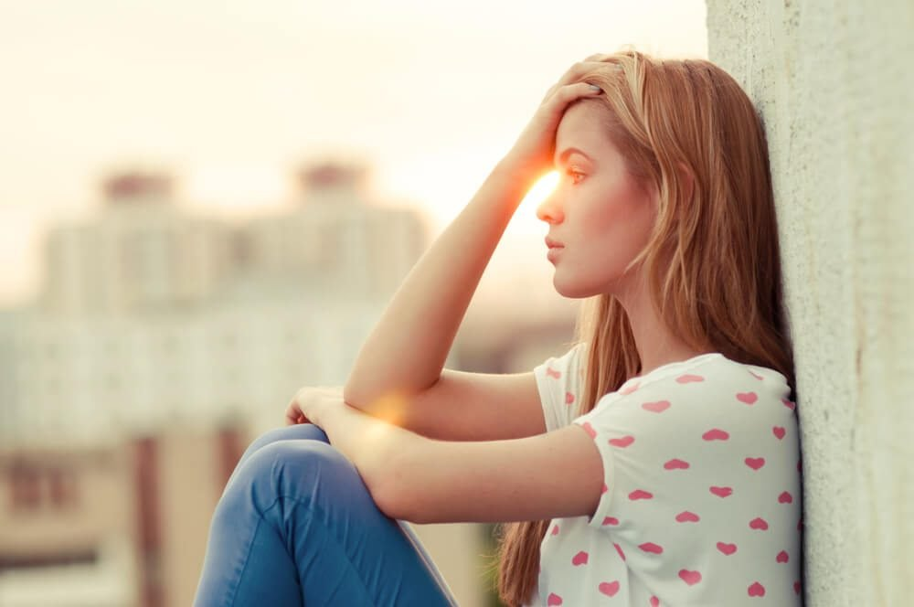 beautiful lonely girl sitting on the roof